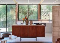 At The Luss House: Blum & Poe, Mendes Wood DM and Object & Thing. The Gerald Luss House, Ossining, New York. Photo by Michael Biondo. Works pictured [foreground left to right]: Green River Project LLC, Aluminum Round Table (2021); micaceous clay vessels by Johnny Ortiz (2021); glass vessels by Ritsue Mishima (2007-2012); [kitchen island left to right]: Ritsue Mishima, Bozzolo Di Seta (2012); Ritsue Mishima, Anima (2012); a black stoneware vase and a porcelain vase by Frances Palmer (2021); micaceous clay vessels by Johnny Ortiz (2021); [background]: Gerald Luss, Infinity Timepiece (2020.)
