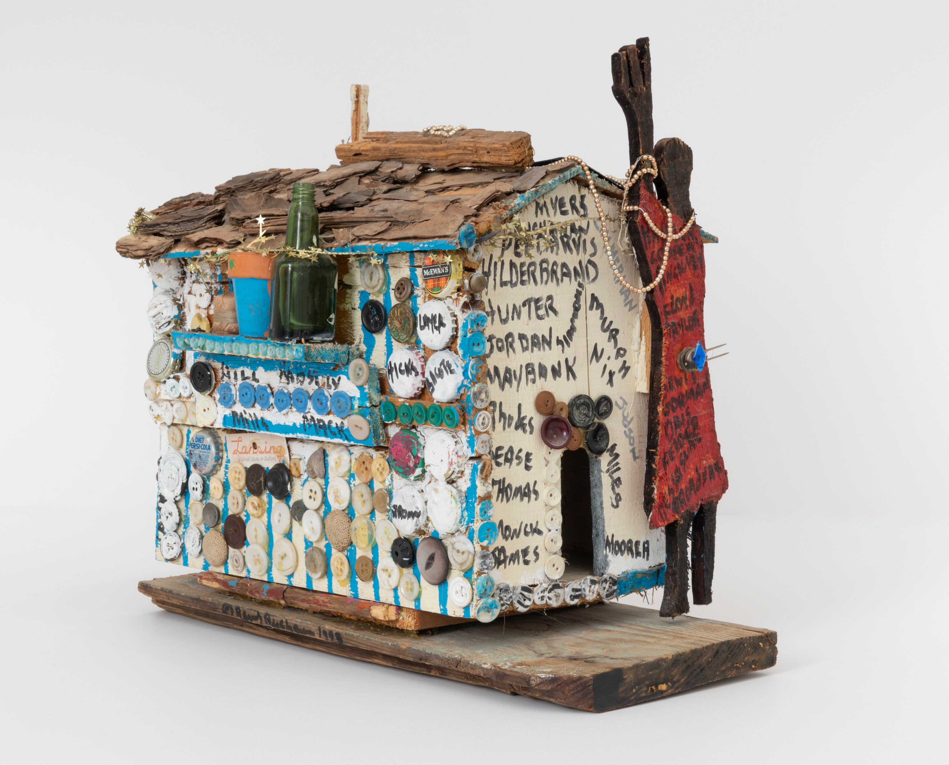 Beverly Buchanan, Orangeburg County Family House, 1993. Paint, sharpie, garland, necklace, wood chips, bark, buttons, bottle caps, license plate, film canister, thumbtacks, clay pot, glass bottle, thread and glue on wood. Image courtesy Andrew Edlin gallery, New York.