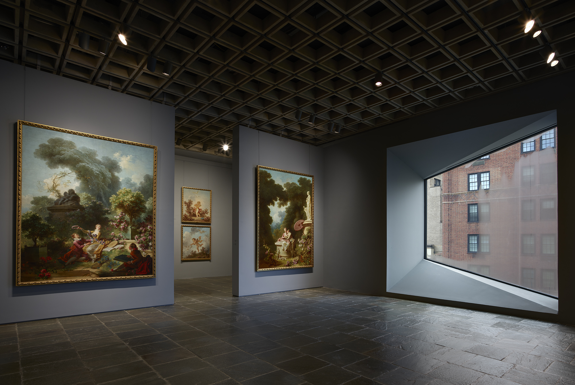 Four grand panels of Fragonard's series The Progress of Love are shown together at Frick Madison in a gallery illuminated by one of Marcel Breuer's trapezoidal windows. This view shows two of the 1771–72 paintings, with two later overdoors visible in the next gallery; photo: Joe Coscia