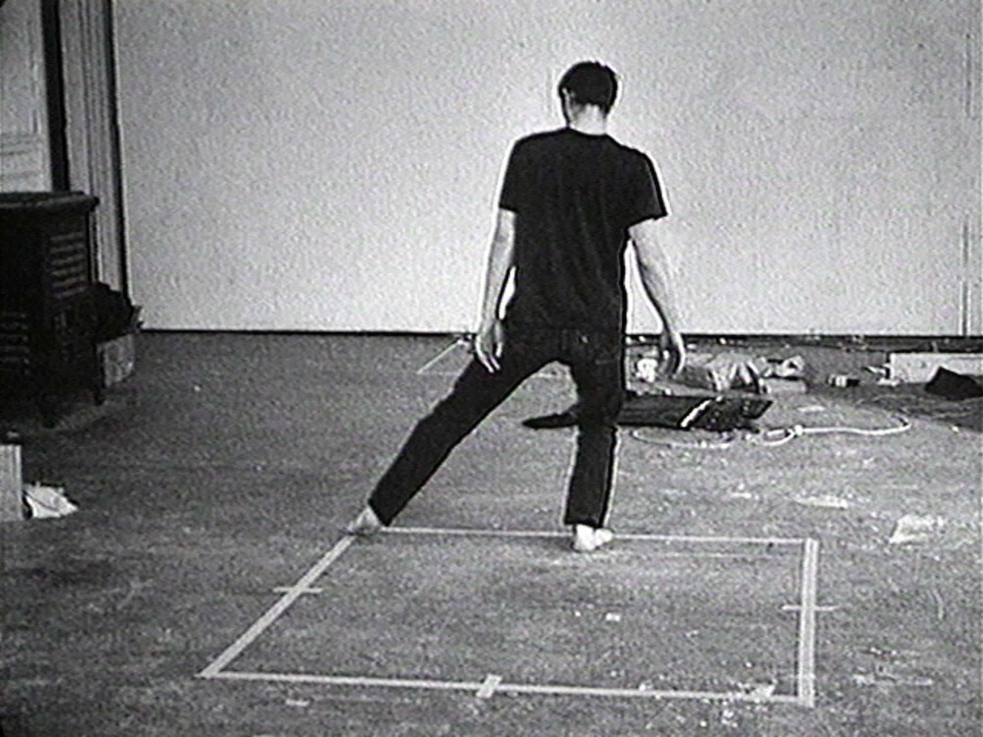 Bruce Nauman (American, born 1941). Dance or Exercise on the Perimeter of a Square (Square Dance). 1967‑1968. 16mm film transferred to video (black and white, sound). 10 min.. Uneditioned. The Museum of Modern Art, New York. Acquired through the generosity of Evanne and Edward J. Gargiulo, Jr. in honor of Ava, Emma and Jack Gargiulo. © 2021 Bruce Nauman / Artists Rights Society (ARS). Courtesy Electronic Arts Intermix (EAI), New York. 581.2008.